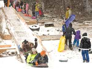 FAST TRACK -- Kids speed down an ice-covered plywood sledding chute onto Swan Lake on Saturday, Jan. 15. Lakeview Drive resident Tim Ulricksen built the slide and collected donated sleds for kids and adults to use. With temperatures in the 40s, sledding has been on hold this week. (Daily Sitka Sentinel photo by James Poulson)